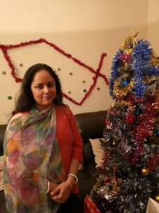 Ronita wearing her new printed scarf in front of a Christmas tree